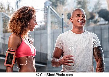 Joyful nice man holding a bottle with water