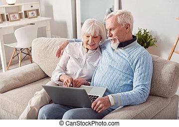 Pleasant elderly couple choosing new laptop in online store