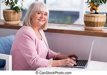 Pleasant elderly lady typing on her laptop