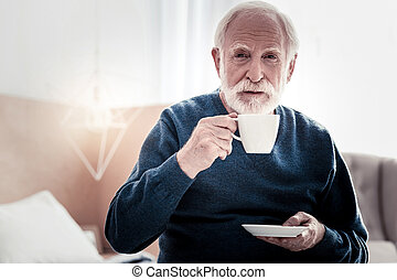 Pleasant elderly man holding a cup of tea