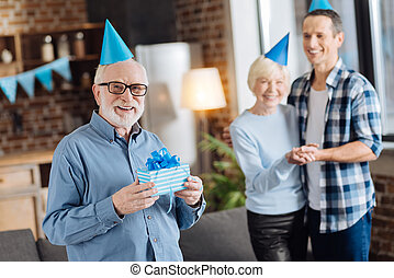 Pleasant elderly man posing with a present for his son