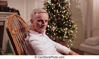 Pleasant elderly man sitting in the rocking chair