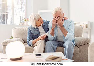 Pleasant elderly woman cheering up her crying husband