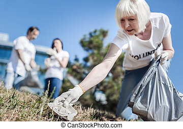 Pleasant elderly woman collecting rubbish