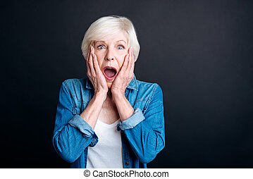 Pleasant elderly woman expressing wonder