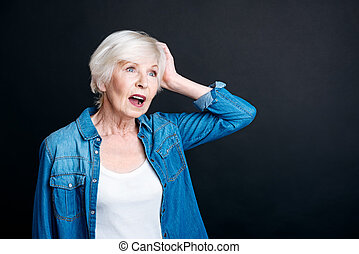 Pleasant elderly woman having an idea