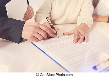 Pleasant elderly woman signing papers