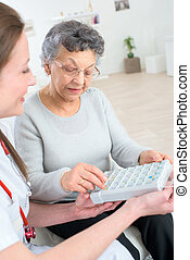 pleasant elderly woman taking pills