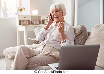 Pleasant elderly woman talking on the phone happily