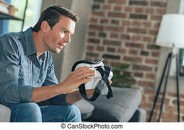 Pleasant excited man studying new technologies