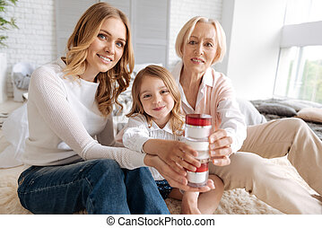 Pleasant extended family creating a tower with cream jars -...