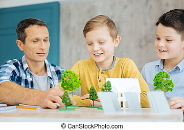 Pleasant father helping his sons with ecology project