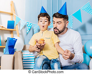 Pleasant father helping little son blow out birthday candle