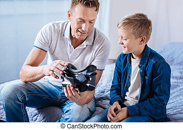 Pleasant father showing his son new VR headset