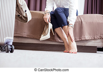 Close up of a nice young woman holding her shoes