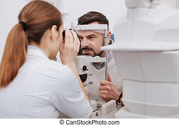 Pleasant female doctor testing the vision of her patient