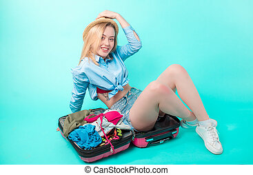 pleasant female tourist with mess in the baggage