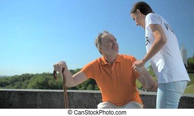 Pleasant female volunteer helping senior man - Helping hand....