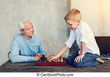 Pleasant game of a little boy and his grandfather