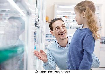 Pleasant gay man helping girl in drugstore