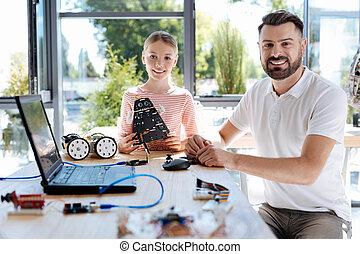 Pleasant girl having robotics workshop with her teacher