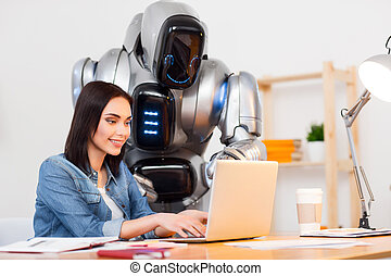 In a good mood. Cheerful pleasant beautiful girl sitting at the table and using laptop while the robot standing nearby