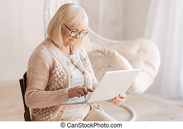 Pleasant good looking woman using a laptop