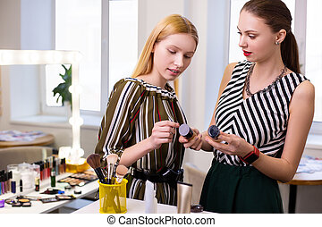 Pleasant good looking women discussing their cosmetics