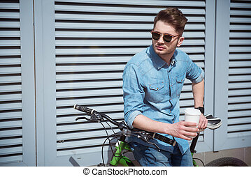 Pleasant guy holding his bicycle