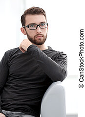 Pleasant guy is resting on sofa