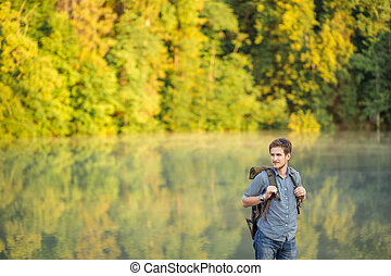 pleasant guy with backpack traveling along