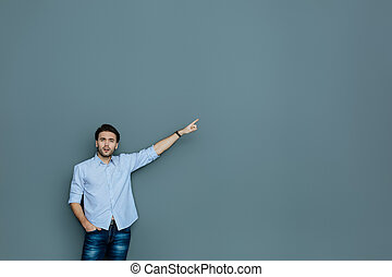 Pleasant handsome man pointing with his hand