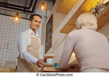 Pleasant handsome waiter being at work