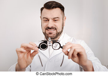 Pleasant happy doctor looking at the eye test glasses