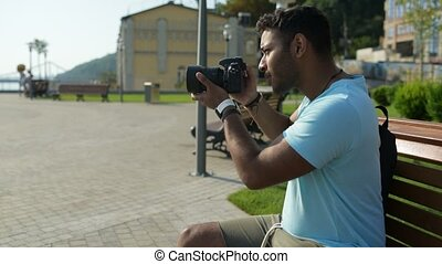 Pleasant Indian man sitting outdoors and using camera - Good...