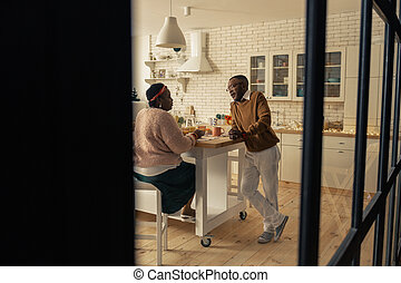 Nice pleasant couple talking in the kitchen
