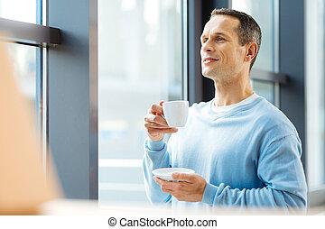 Pleasant joyful man having coffee