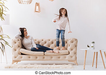 Pleasant joyful woman watching her daughter jumping - Time...