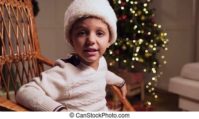 Pleasant little boy telling Christmas stories at home