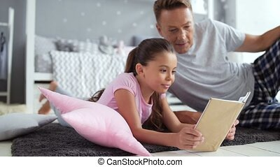 Pleasant little girl reading a book with her father