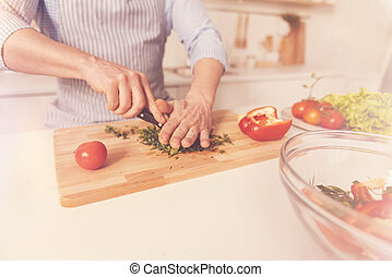Pleasant man cooking salad in the kitchen