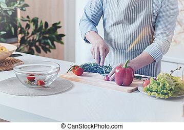 Pleasant man cooking vegetable salad