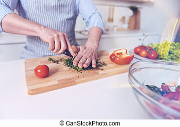 Pleasant man cutting vegetables for salad