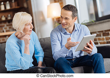 Pleasant man explaining how to use tablet to his mother