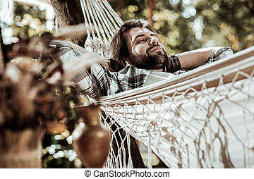 Pleasant man having a nap in a hammock