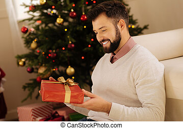 Pleasant man holding a gift box and smiling