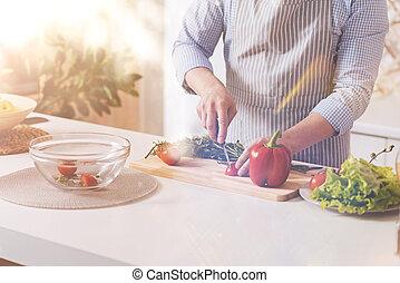 Pleasant man making vegetable salad