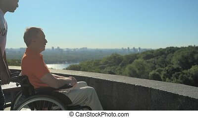 Pleasant man pushing a wheelchair on the observation point -...