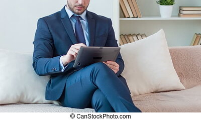 Pleasant man sitting on the sofa