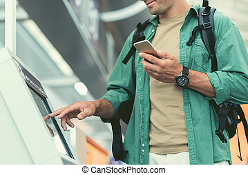 Pleasant man with mobile phone is touching interactive display
